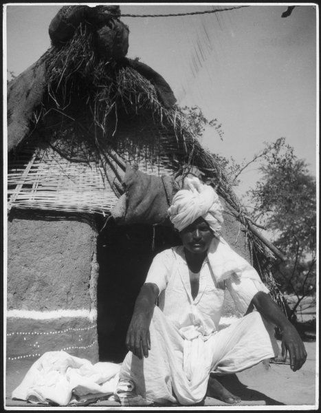 The headman or chief of a small village in India, squatting traditionally at the entrance to the hut where he lives with his wife and four children