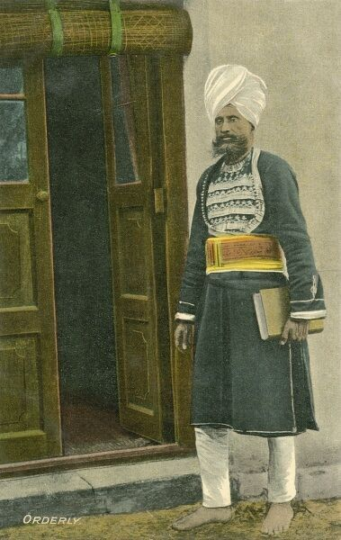 A very smart Indian Orderly/Manservant, holding a book or ledger