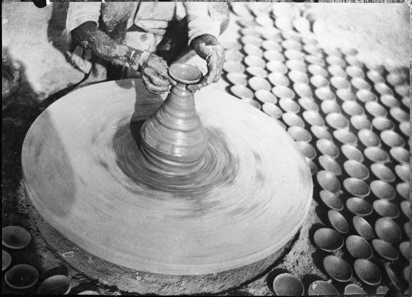 A Indian potter moulding a vase or jug at his wheel, with assorted dishes, made earlier, all around him