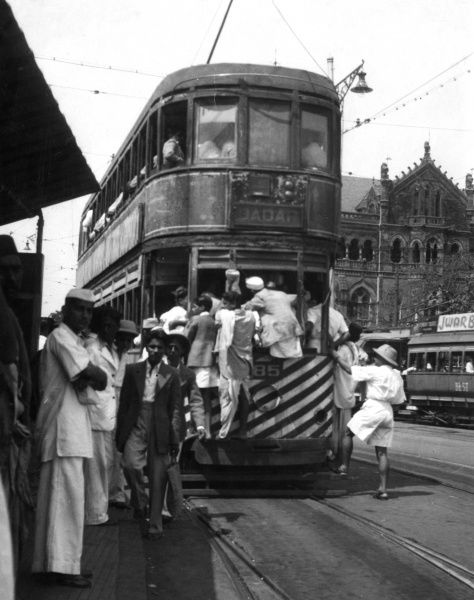 A common sight in India, a tram packed to the gills with passengers, some of them even hanging on the outsides for dear life. This tram is destined for Jadar. Date: 1930s