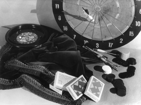 A selection of indoor games, including darts and a dart board, a roulette wheel and table cloth and packs of playing cards. Date: 1930s