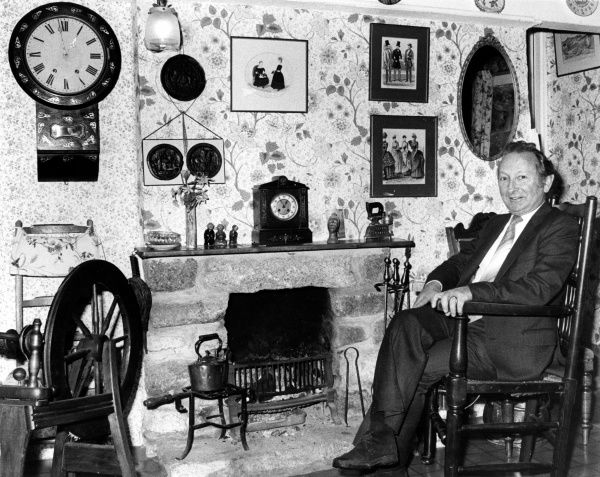 Scene inside a traditional miner's cottage at Land's End, Cornwall. There is a copper kettle by the fireplace, a spinning wheel, two clocks, various pictures, and patterned wallpaper, all presided over by the proud owner