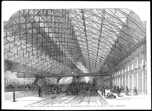 Passengers await their train beneath Birmingham Station's soaring canopy, upheld by a lattice of girders providing a wide span over the tracks