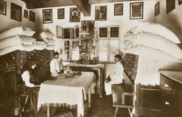 Superb photographic postcard depicting the interior of a Hungarian Peasant house, showing the piles of clean linen and bedding, folding benches, religious pictures adorning the whitewashed walls, two large dressers and seemingly a pair of brothers
