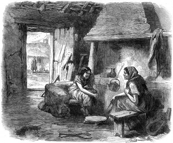 A woman and young girl indoors in a mud cabin in Kildare. They sit next to the fire over which a kettle hangs on a chain. This is a poor ramshackle dwelling with the door nearly falling apart and a view of a man and a pig outside