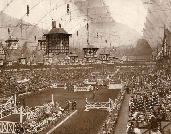 View of the arena inside the Grand Hall at the International Horse Show, Olympia exhibition centre, West Kensington, London. The arena is set out with fences for the horse jumping events, the auditorium is partly filled with audience members