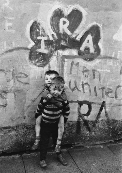 Two dirty boys stand in front of IRA graffiti in Northern Ireland Date: 1960s