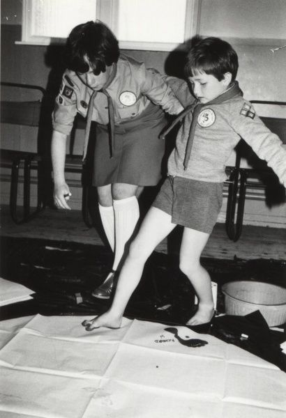 An Irish scout showing a younger Beaver Scout how to do foot painting. 1970s