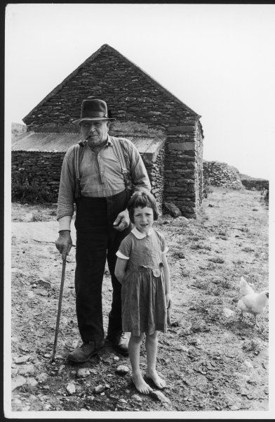An old Irish crofter, leaning on his walking stick and smoking his pipe outside his cottage with his barefoot granddaughter