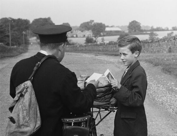 A country postman in Ireland delivers a postcard to a lucky boy