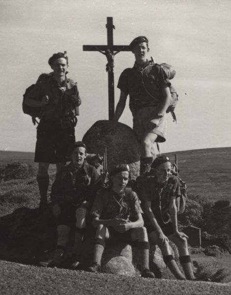 Irish Scouts, on a hike with rucksacks, stopped at a wayside cross in Glencree, County Wicklow, Ireland. 1960s