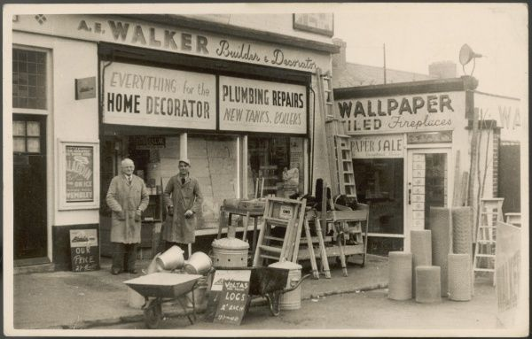 Proprietors of an ironmonger stand outside their shop