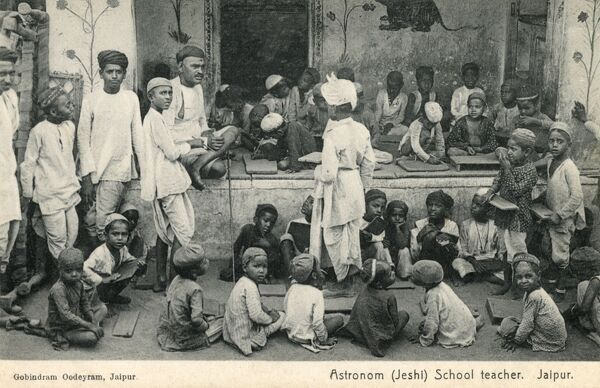 A School Teacher (Astronom / Jeshi) at Jaipur, India and his large class of pupils, not paying him a lot of attention now a far more interesting photographer has just appeared! Date: circa 1910s
