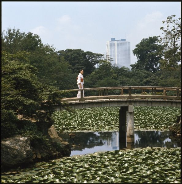 Japanese woman on a bridge, with the Keo Plaza Hotel, Tokyo, in the background. Date: 1976