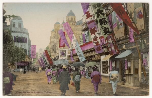 A street scene in Asakusa, Tokyo, Japan, showing women with parasols and colourful advertising banners