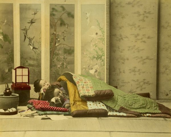 Two Japanese girls sleep in a traditional Japanese bed on the floor; a decorative screen is behind them