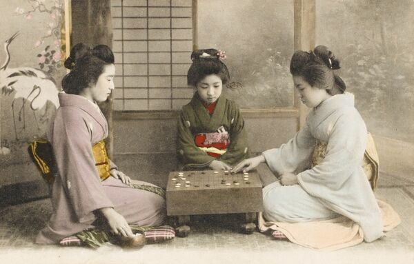 Three Japanese Geisha girls in Kobe, Japan, playing the popular boardgame Go in their beautiful Kimonos