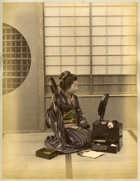 A Japanese lady kneels on the floor and examimes her hairstyle using two mirrors