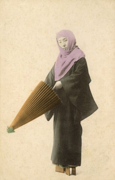 Japanese lady about to unfurl her umbrella. - she is weasring distinctive block shoes and a purple headscarf/shawl Date: circa 1900s