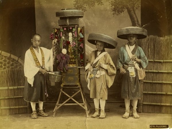 Three Japanese pilgrims with prayer flags and figures