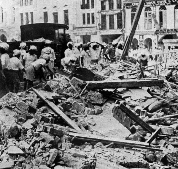 Singapore residents assess the damage done by a Japanese air raid the previous night. Date: January 1942
