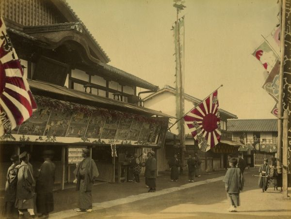 A street in an unknown Japanese town with rayed rising sun flags