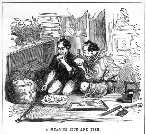 Two men eat a traditional meal of rice & fish