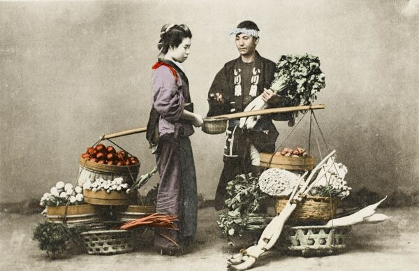 A Japanese vegetable seller, his wares in many baskets hung on a long yolk, sells to a young geisha woman