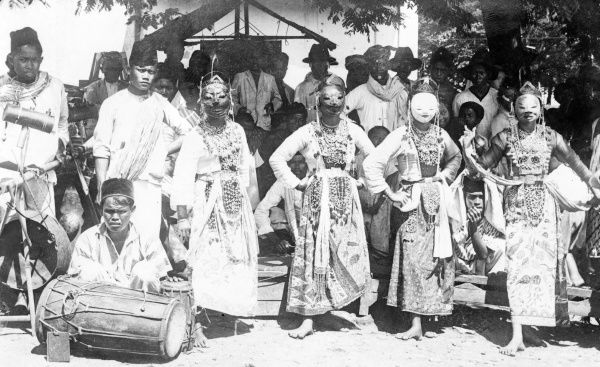 Native dancing girls in traditional masks, veils and elaborate costumes, Java, Indonesia. Date: 1930s