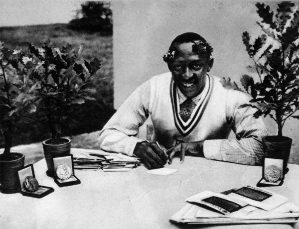 Photograph of Jesse James Cleveland Owens, the US athlete, pictured with his Olympic oak-trees and medals, 1936. Owens won four gold medals at the the 1936 Berlin Olympics - the 100 metres, the 200 metres, the long jump and the 4x100 metres relay