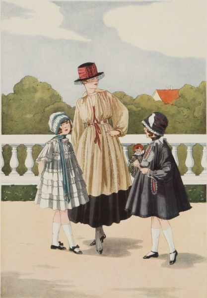 A fashionable young mother poses with her two well-dressed little girls during a walk in the park