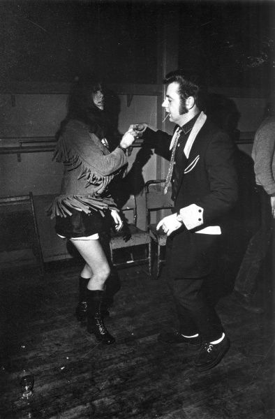 A Teddy Boy wearing 'Beetlecrushers', jiving with a girl with a suede jacket with tassles at a dance club. Date: 1980s