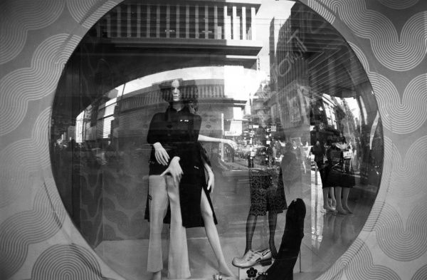 Trendy outfits on display in the shop window of a boutique in Johannesburg, South Africa. Date: late 1960s