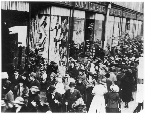 Outside John Lewis & Co. department store, shoppers crowd along the pavement on Oxford Street, London