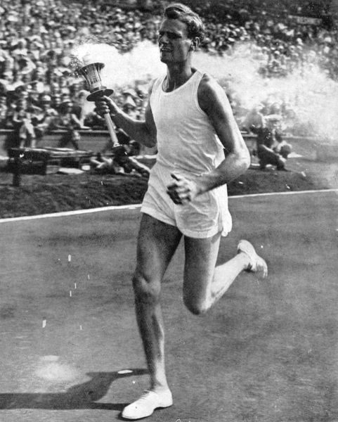 The athlete and Surbiton medical student John Mark, a former Cambridge blue and quarter-miler, circles Wembley Arena with the Olympic torch. Date: 1948