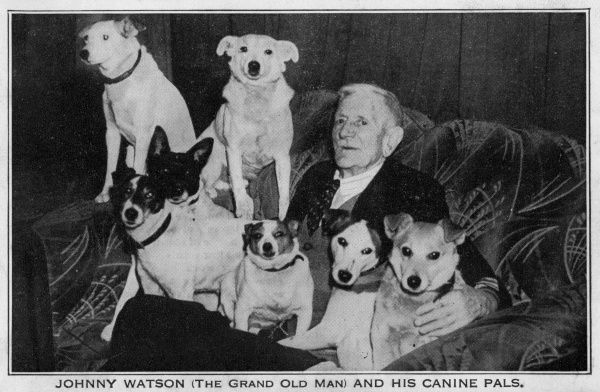 Johnny Watson, known as the Grand Old Man as he lived to a great age, and his canine pals (seven dogs), sitting on a sofa. Date: circa 1940s