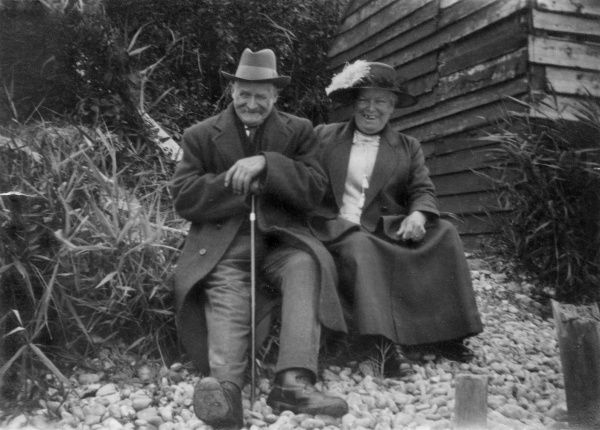 A jolly elderly couple sit on a pebble-covered hillside by a hut, having a good old chuckle!