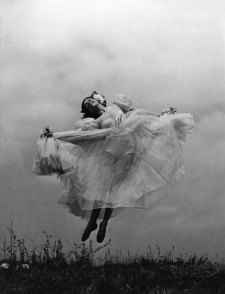 An outdoor girl wearing a wide see-through chiffon dress and flowers in her hair, jumps in the air, full of the joys of spring...  1930s
