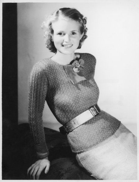 A hand-knitted jumper in a lacy ribbed stitch without a collar or welt is worn with a broad belt & a knitted flower brooch