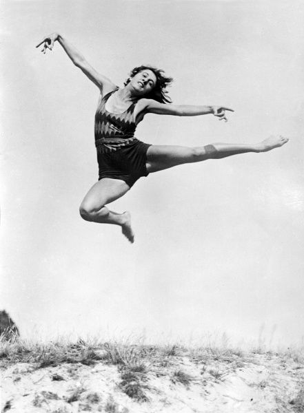 A female German athlete striking an artistic pose as she leaps in the air above some sand dunes! Date: early 1930s