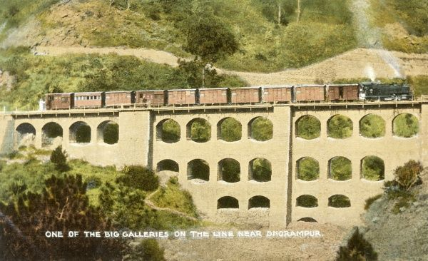 A scene on the Kalka to Dharampur Railway, in the lower Himalayas, northern India : a train crosses the four-tier gallery : notice also the pipe-line. Date: early 20th century