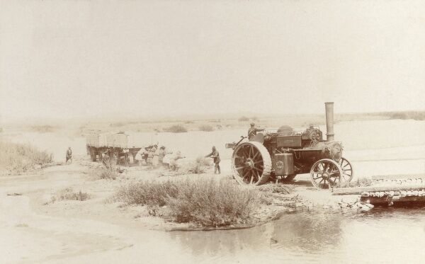 Karaganda, Kazakhstan - Steam tractor and two heavy wagons crossing a bad section of road Date: 1909