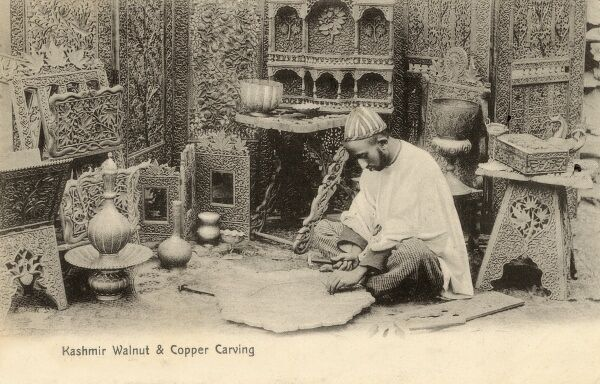 A highly-skilled craftsman producing carvings in copper and walnut wood - Kashmir, India. Date: 1910s