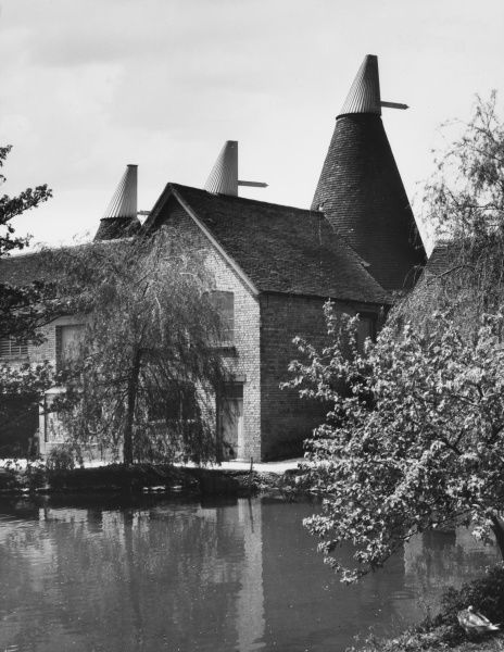 These familiar landmarks of Kent are the red brick and tiled hop kilns used for drying hops after harvesting. This one sits beside the village pond