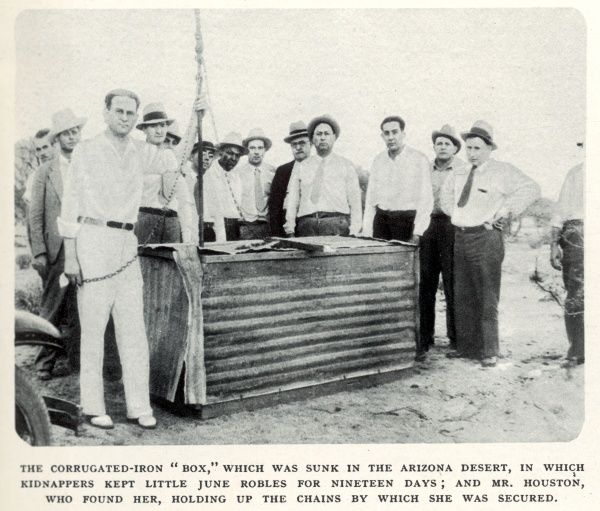 The corrugated-iron 'box' which was sunk in the Arizona Desert in which kidnappers kept little June Robles for nineteen days; and Mr Houston, who found her, holding up the chains by which she was secured