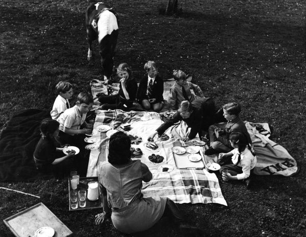 "A group of young children enjoy a picnic outdoors under the careful supervision of a woman - ""don't speak with your mouth full, Jimmy!"". Date: early 1930s"