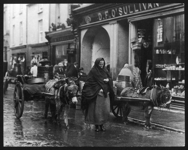 An old woman with a donkey cart counts her change whilst walking through the rainy streets of Killarney, Co. Kerry