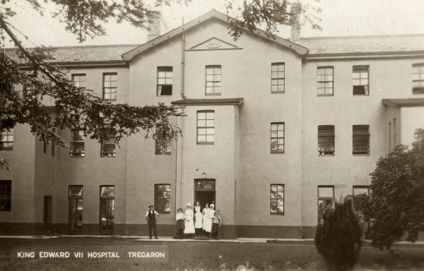 Staff and patients at the entrance to The King Edward VII Hospital, Tregaron, Wales. The hospital was formerly the Tregaron Union workhouse, erected (as shown by the date plaque above) in 1876, on Dewi Road, Tregaron