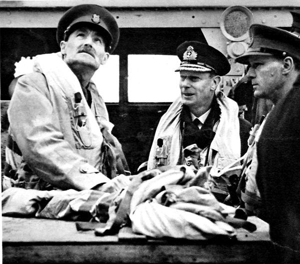 Photograph showing King George VI (centre) with Sir A. Lascelles (left) and Major-General Laycock on the bridge of HMS 'Arethusa', crossing the English Channel, 16th June 1944