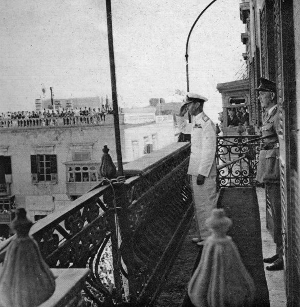 King George VI salutes to the cheering crowd of Maltese citizens from the balcony of the palace in Valetta during a visit to Malta on 20th June 1943. Date: 1943